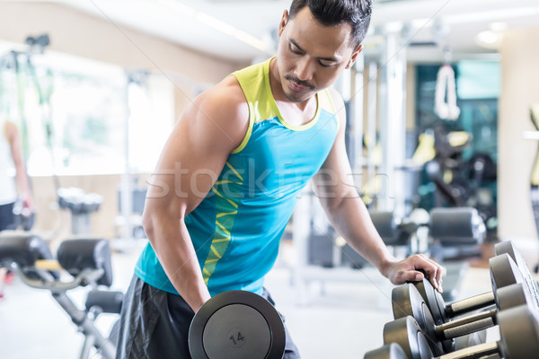 Portrait of a handsome young man exercising bicep curls Stock photo © Kzenon