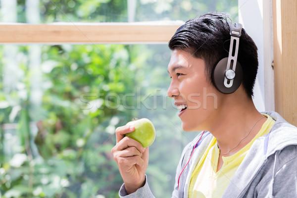 Giovane mangiare fresche verde mela ascolto Foto d'archivio © Kzenon