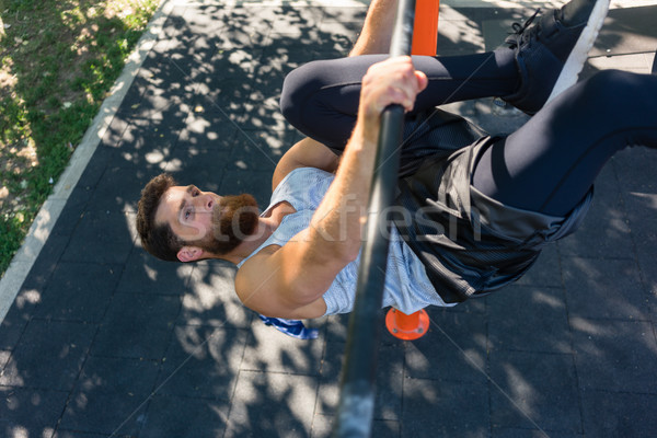 Strong man doing hanging leg raises for abdominal muscles Stock photo © Kzenon