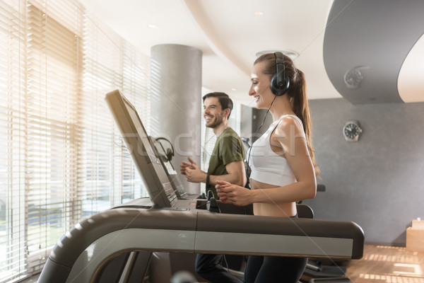 Young woman listening to music while running on a modern treadmill Stock photo © Kzenon