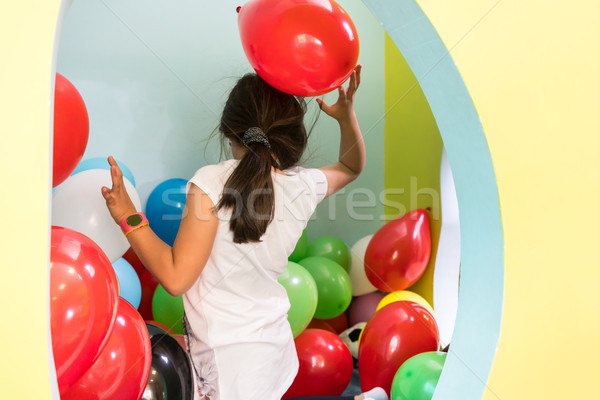 Cute girl playing with colorful balloons during playtime at the kindergarten Stock photo © Kzenon