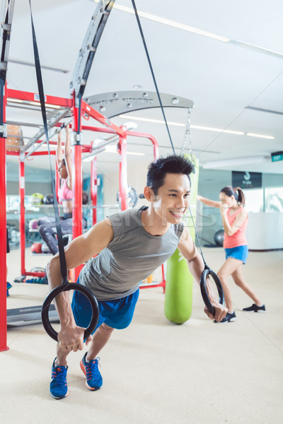 Fit young man exercising with gymnastic rings in a trendy fitness Stock photo © Kzenon