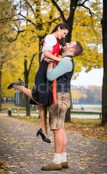 Bavarian couple in Tracht in loving embrace with uplift Stock photo © Kzenon