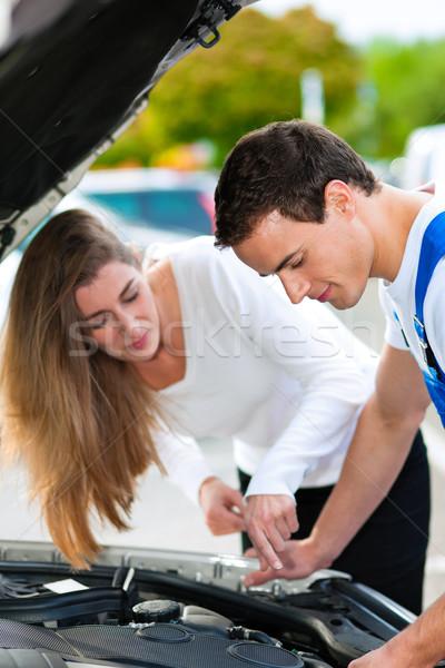 Woman talking to car mechanic in repair shop Stock photo © Kzenon