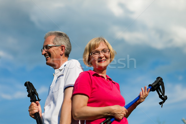 Happy mature or senior couple doing Nordic walking in summer Stock photo © Kzenon