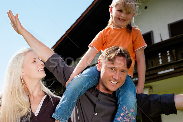 Family standing in front of their home Stock photo © Kzenon