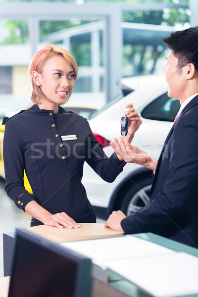 Asian man at car rental receiving key Stock photo © Kzenon