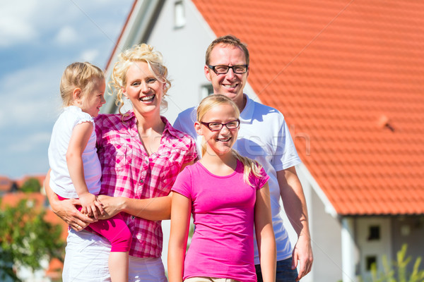 Family standing proud in front of home Stock photo © Kzenon