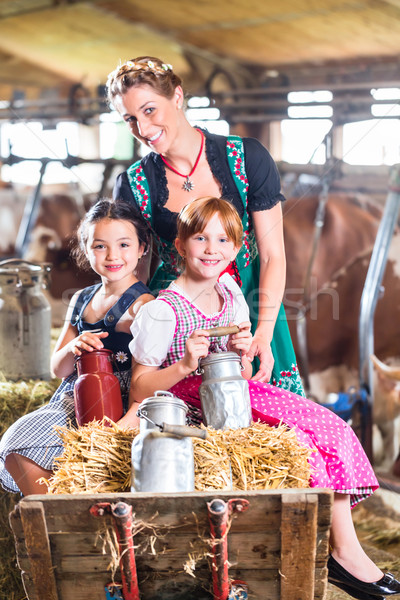 Stock photo: Bavaria family driving pushcard in cow barn