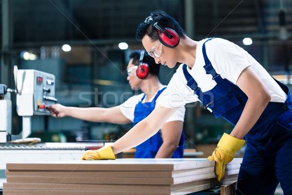 Stock photo: Two wood workers in carpentry cutting boards