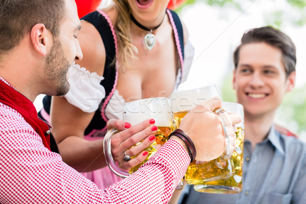 Stock photo: Three friends in Munich Beer garden clinking