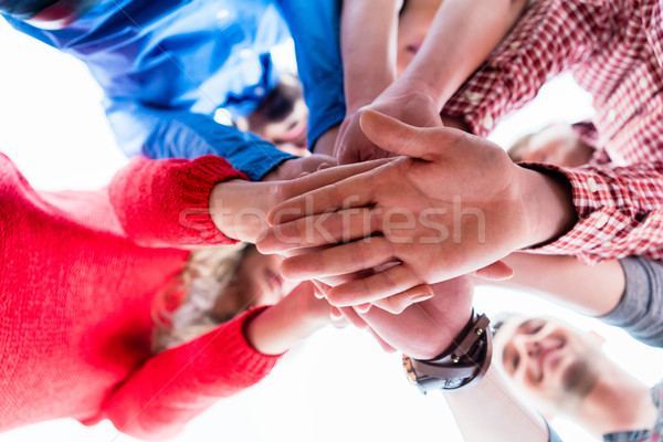 Students learning and stacking hands together Stock photo © Kzenon
