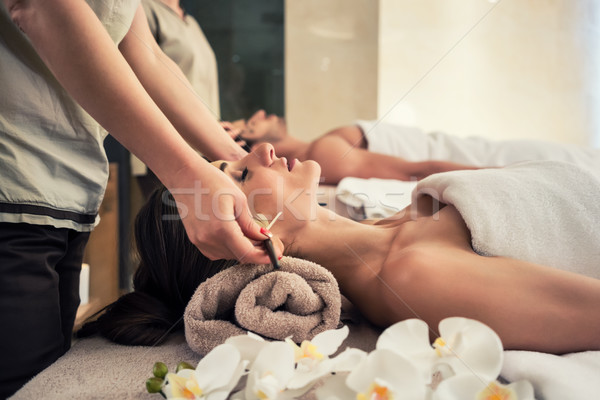Relaxed woman lying down on massage bed during facial treatment Stock photo © Kzenon