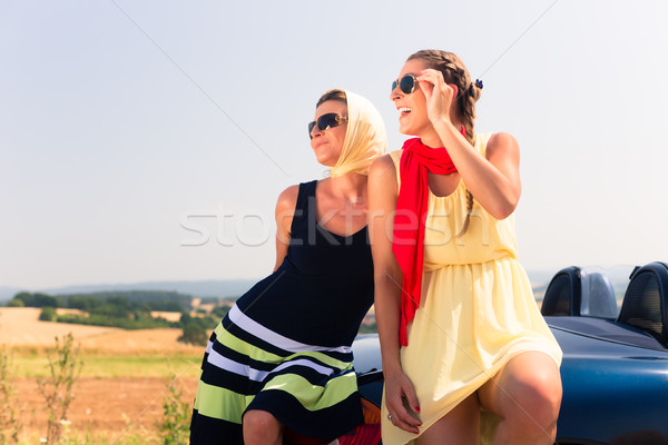 Two women sitting on hood of convertible car  Stock photo © Kzenon