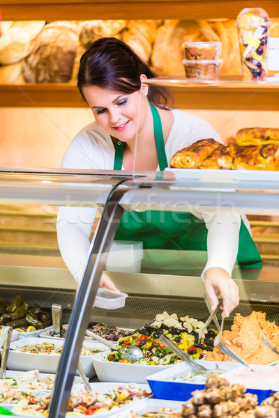 Saleswoman in delicatessen selling appetizers Stock photo © Kzenon