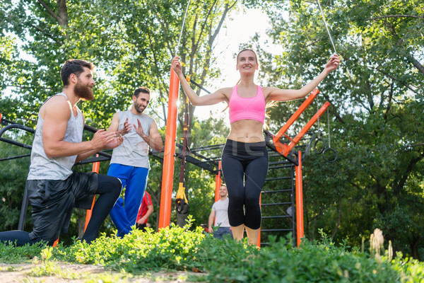 Beautiful woman jumping rope in the applauses of her friends dur Stock photo © Kzenon