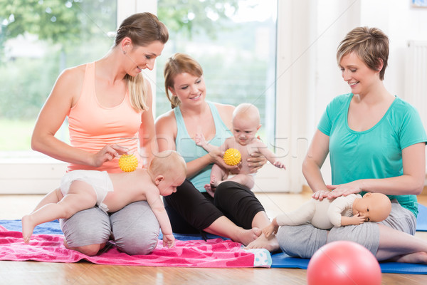 Stock photo: Young women practicing massage for their babies in mother-child