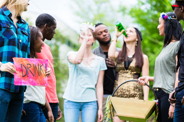 Multicultural group playing drinking game together Stock photo © Kzenon