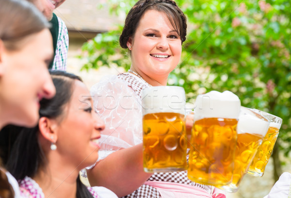 Waitress serving beer in beer garden Stock photo © Kzenon