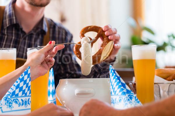 Emberek eszik borjúhús kolbász étterem csoportkép Stock fotó © Kzenon