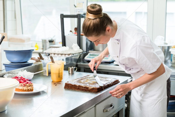 Confectioner woman getting chocolate cake ready with topping Stock photo © Kzenon