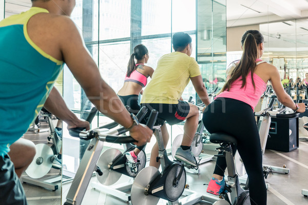 Stock photo: Fit women burning calories during indoor cycling class