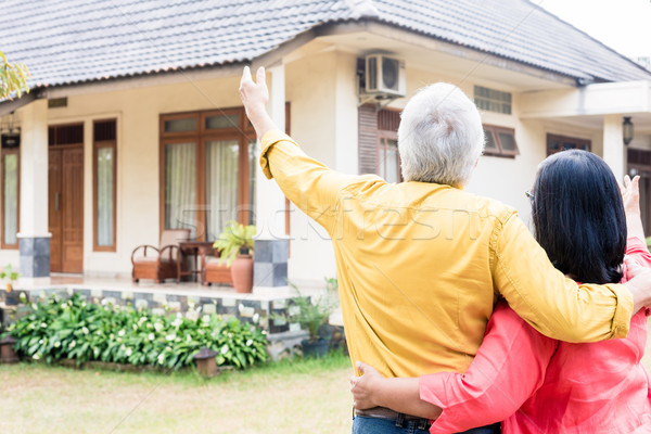 Elderly man pointing to his wife a comfortable residential house Stock photo © Kzenon