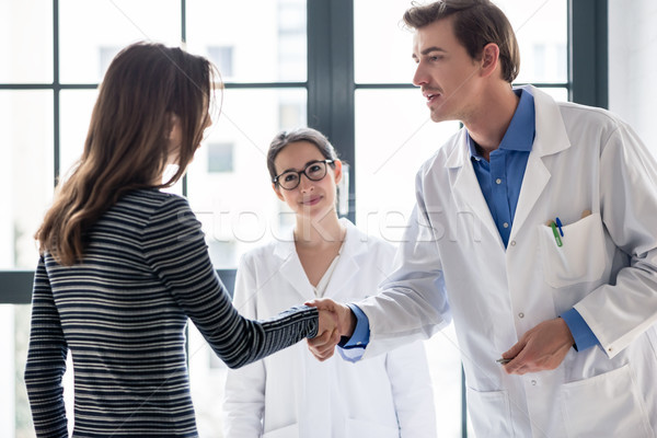 Reliable physician and female patient shaking hands before consultation Stock photo © Kzenon