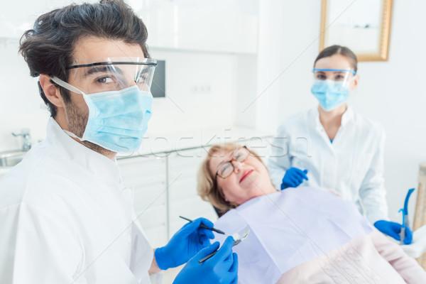 Dentiste homme chirurgie regarder femme infirmière Photo stock © Kzenon