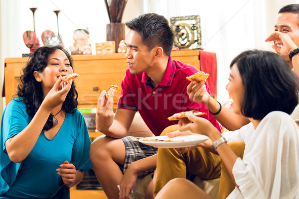 Asian people eating pizza at party Stock photo © Kzenon