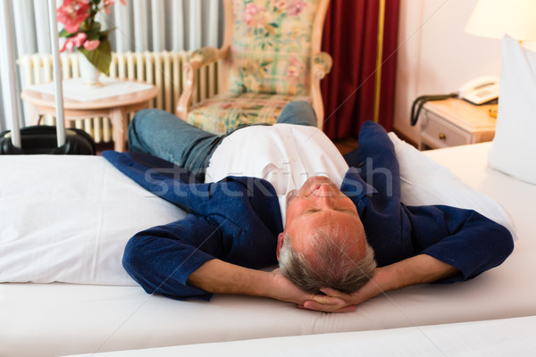 Senior homem cama quarto de hotel relaxante sorrir Foto stock © Kzenon