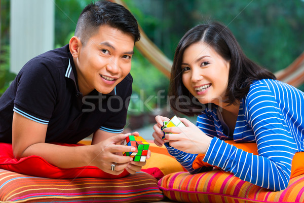 Asian couple at home playing with magic cube Stock photo © Kzenon