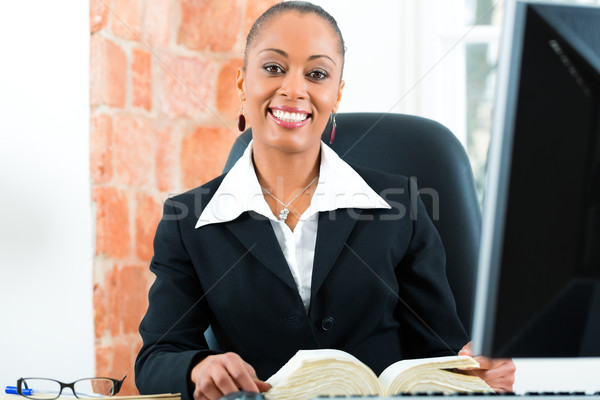 Lawyer in office with law book and computer Stock photo © Kzenon