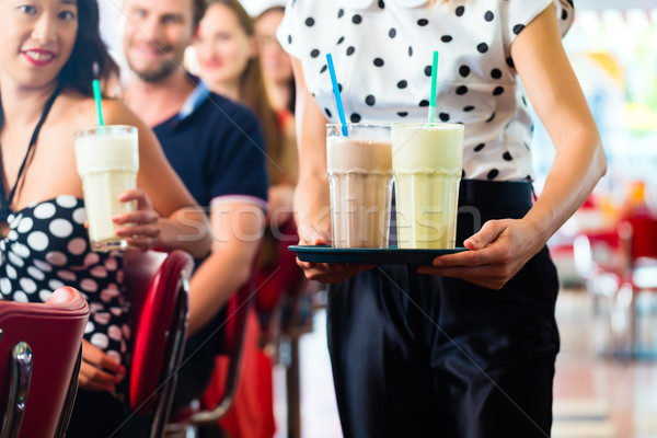 People in American diner or restaurant with milk shakes Stock photo © Kzenon