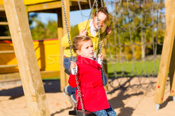 Girl swinging on play area or court Stock photo © Kzenon