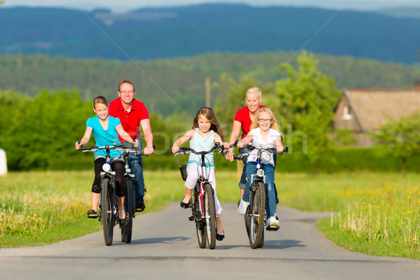 Family with kids cycling in summer with bicycles Stock photo © Kzenon