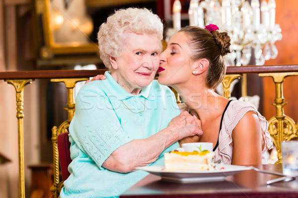 Senior woman and granddaughter with cake in cafe Stock photo © Kzenon