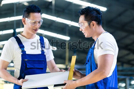 Two industrial workers inspecting work piece Stock photo © Kzenon