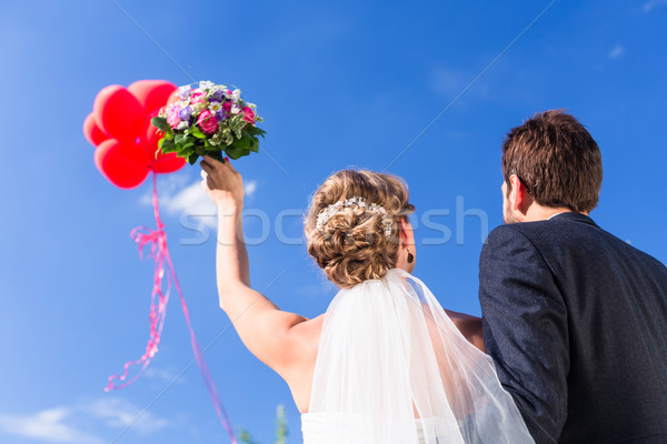 Bride and groom at wedding with helium balloons Stock photo © Kzenon