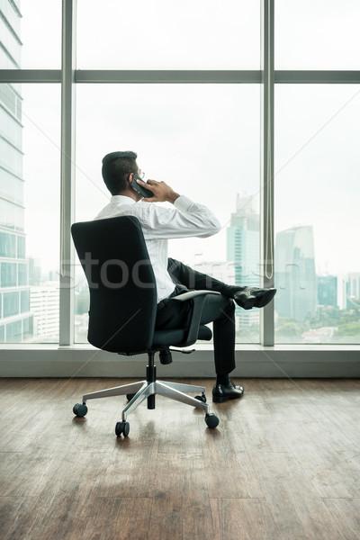 Rear view of businessman talking on phone while sitting down Stock photo © Kzenon
