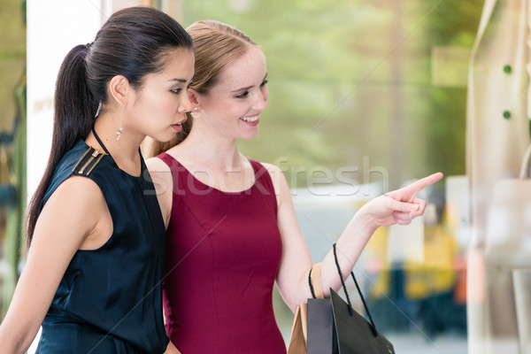 Two female best friends looking at the latest fashion trends whi Stock photo © Kzenon