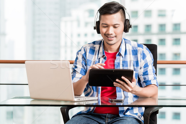 Young asian man having video conference Stock photo © Kzenon