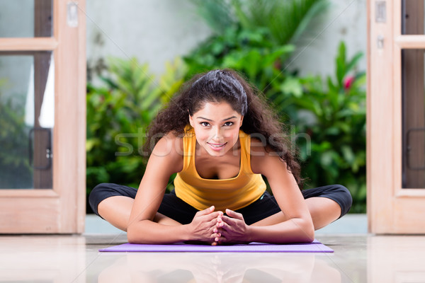 Young woman doing stretching exercise indoors Stock photo © Kzenon