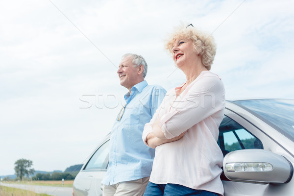 Two senior people smiling with confidence while leaning on their Stock photo © Kzenon