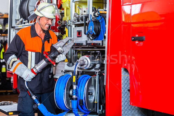 Fire fighter checking hydraulic cutter at fire engine Stock photo © Kzenon