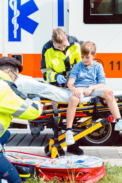 Emergency doctors caring for accident victim boy Stock photo © Kzenon
