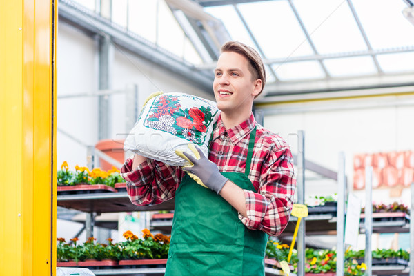 Cheerful young man carrying a bag of potting soil while working as florist Stock photo © Kzenon