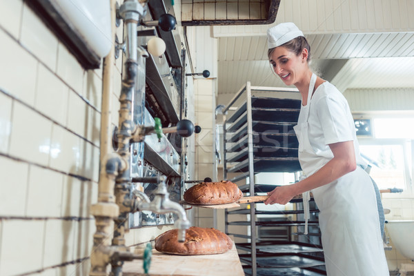Baker woman getting bread out of bakery oven Stock photo © Kzenon