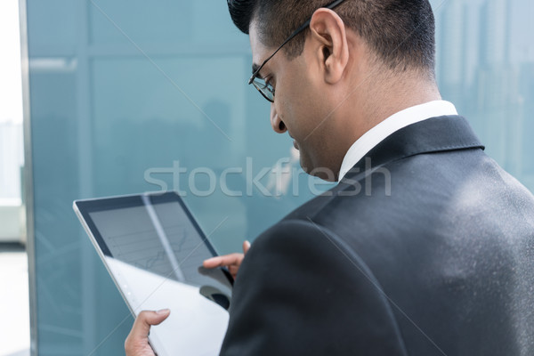 Indian businessman analyzing financial report indoors Stock photo © Kzenon
