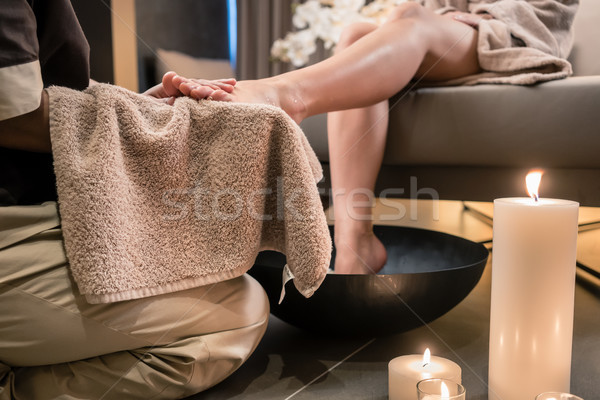 Asian therapist wiping the feet of a female client after therapeutic washing Stock photo © Kzenon